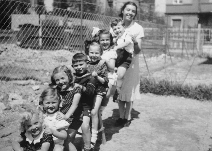 A group of Jewish and Hungarian children pose with their teacher on a seesaw in the playground of a pre-school in Budapest. Gyorgy Pick is seated closest to the teacher.