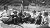 A group of Jewish and Hungarian children play with their teacher in a sandbox in the playground of a pre-school in Budapest. Gyorgy Pick is seated third from the right.