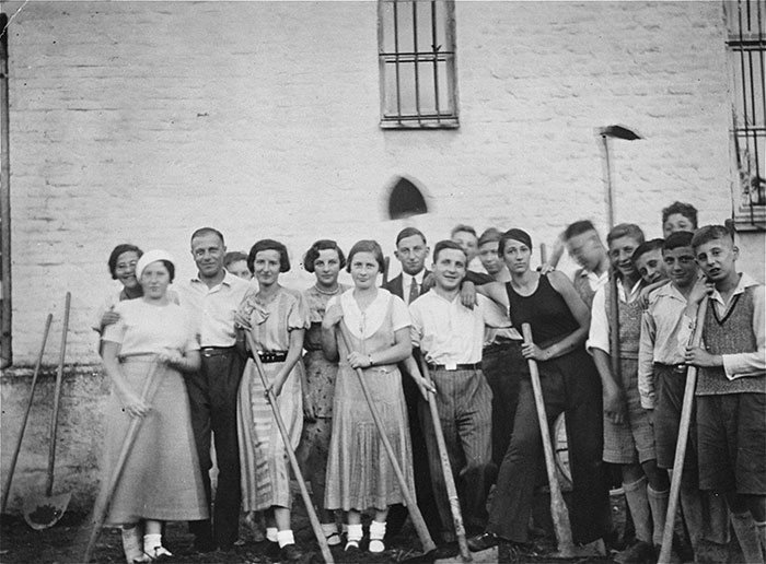 Jewish youth prepare to dig up a potato patch in order to create a handball field for Jewish teams, following the exclusion of Jews from organized sports in Germany. Pictured in the front row, wearing a black tank top, is Gretel Bergmann (now Margaret Lambert).