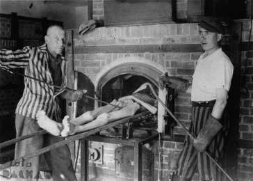Survivors of the Dachau concentration camp demonstrate the operation of the crematorium by pushing a corpse into one of the ovens. Dachau, Germany, April 29-May 10, 1945. <i>US Holocaust Memorial Museum, courtesy of Albert Schiff</i>