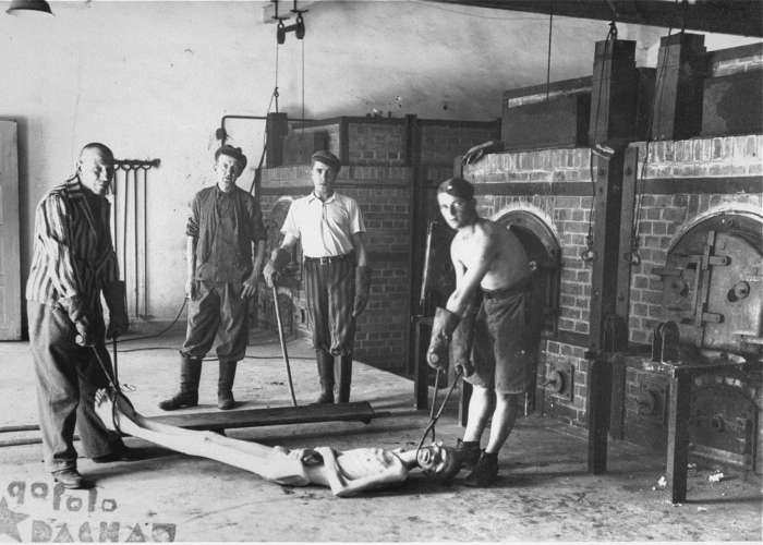 Survivors of the Dachau concentration camp demonstrate the operation of the crematorium by preparing a corpse to be placed into one of the ovens. Dachau, Germany, April 29-May 10, 1945. <i>US Holocaust Memorial Museum, courtesy of R. Harrison</i>