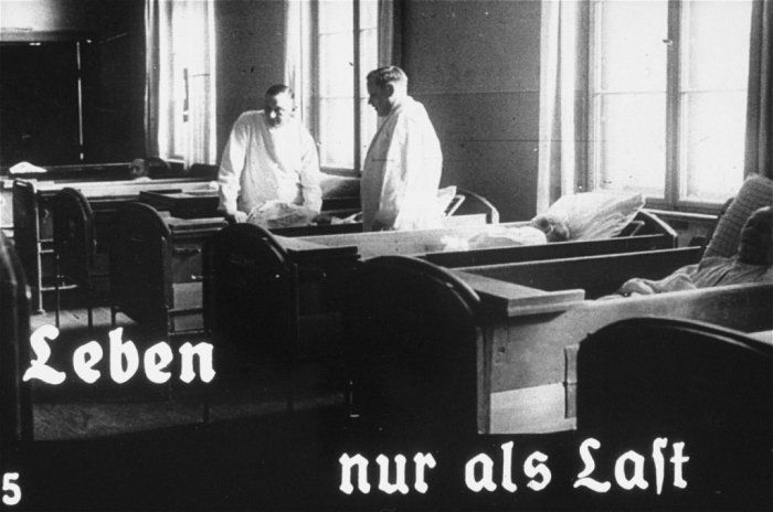 "Propaganda slide featuring two doctors working at an unidentified asylum for the mentally ill. The caption reads, ""Life only as a burden."" Germany, 1934."