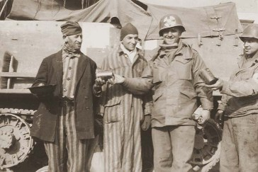 US Army medical personnel with the 10th Armored Division distribute food to two survivors liberated from a concentration camp.