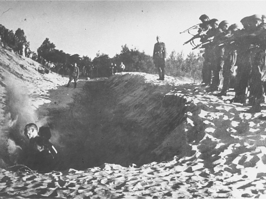 Spectators look on as German police and men presumed to be members of an Einsatzkommando (mobile killing unit) execute men standing in a trench. The sand indicates that this photograph may show an action carried out along the coast of the Baltic Sea.