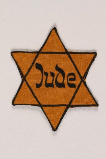 Just as Jews had been forced to wear the yellow star badge throughout Nazi-occupied Europe, similar badges identified them as Jewish prisoners when interned in concentration camps for forced labor. <i>US Holocaust Memorial Museum, gift of Alice Fink</i>