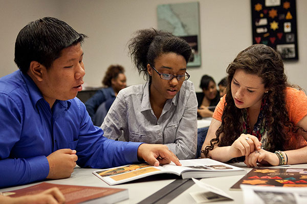 Three students examine documents in a classroom at the Museum