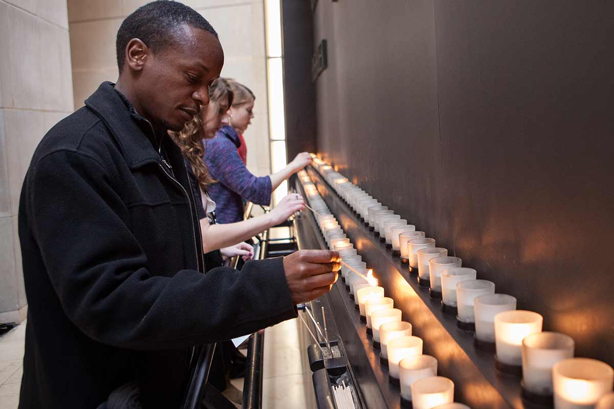 A Museum visitor lights a candle in the Museum Hall of Remembrance.