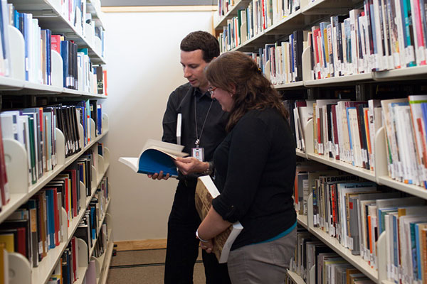 Two people read a book between stacks at the Museum Library