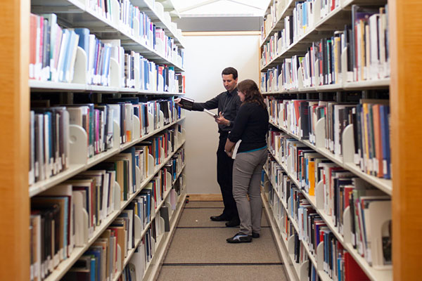 Two people stand in between shelves of books in the Museum Library