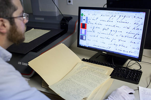 A museum employee sits at a computer, with a copy of a document up on his screen