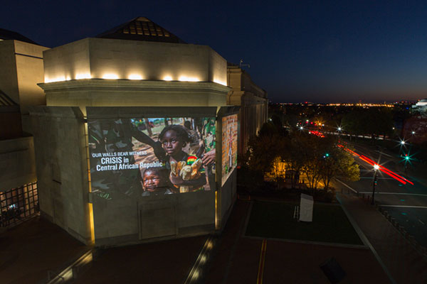 A picture of the crisis in the Central African Republic, featuring a young girl, is projected on the exterior of the Museum