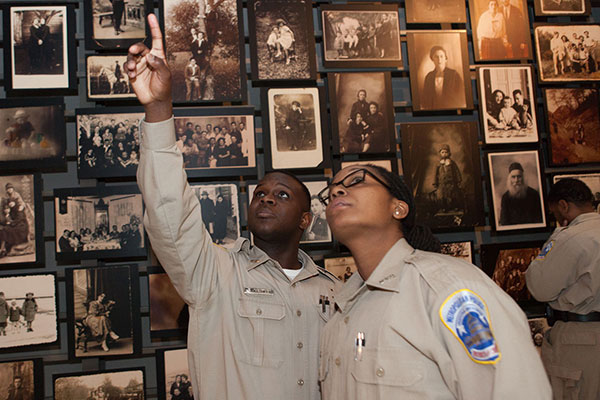 Two uniformed Museum visitors point up to a photo in the Tower of Faces