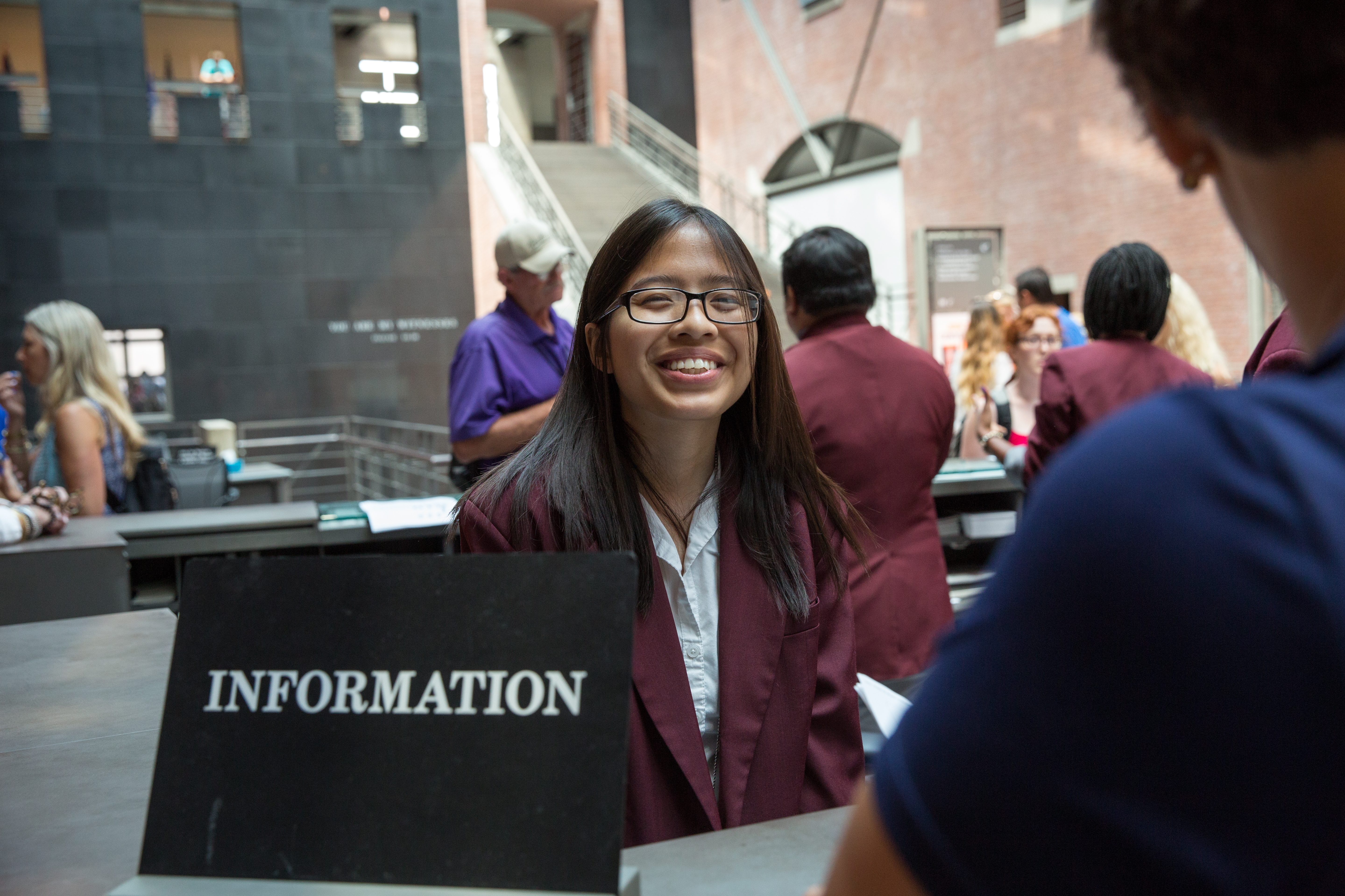 A museum volunteer stands at the Information Desk