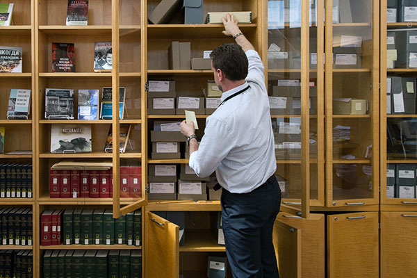 A Museum staff member pulls an item off a shelf in the Library and Reading Room