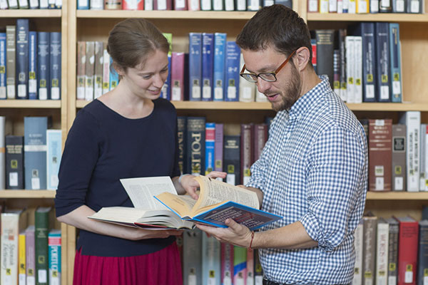Two people stand and read from a book in the Museum Library