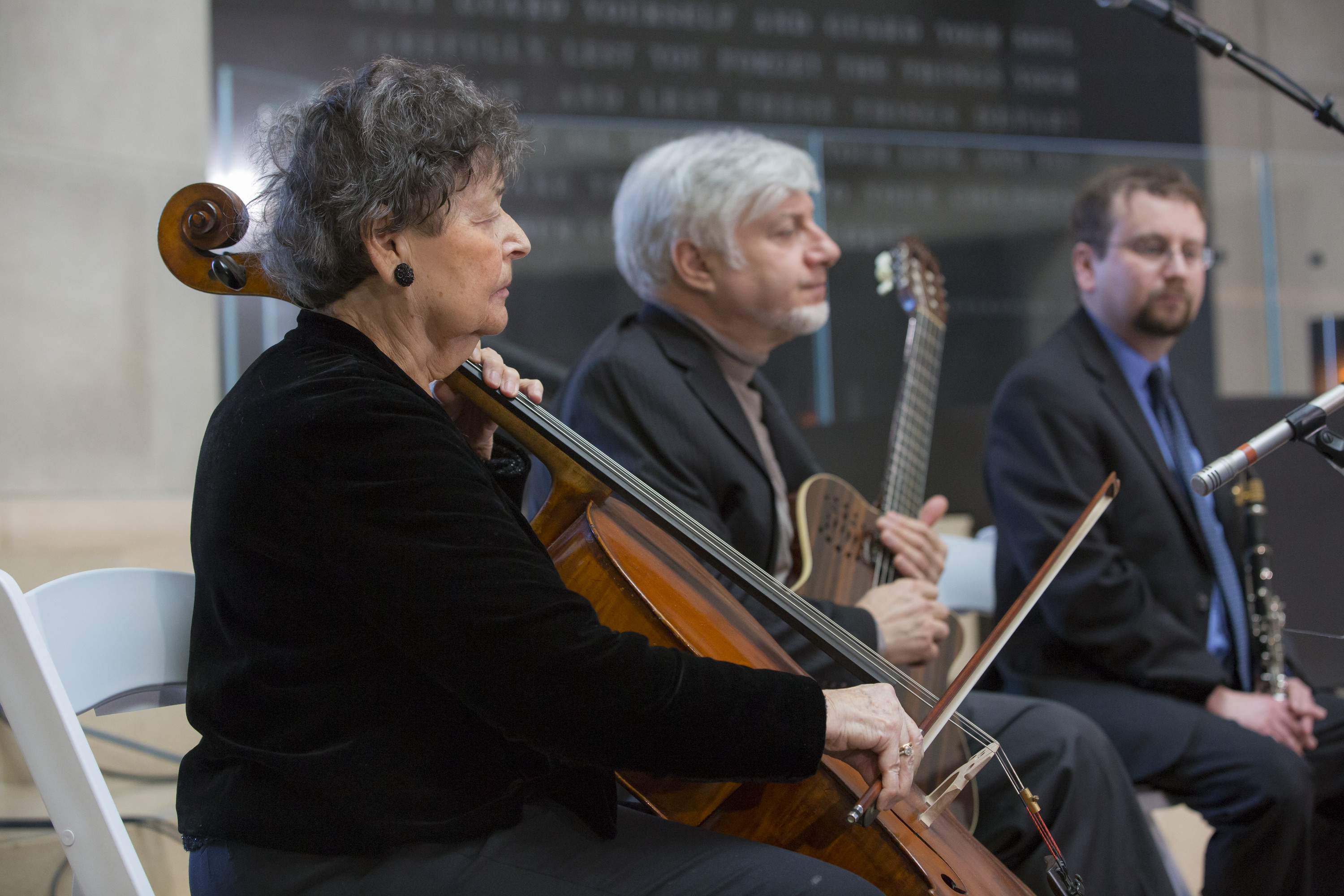 A survivor volunteer plays music at a Museum remembrance event.
