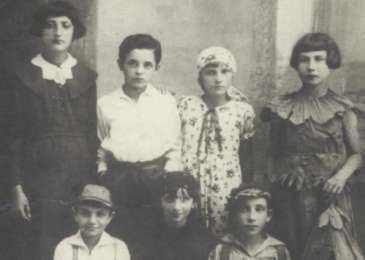 Group portrait of school girls dressed in costume for a school performance, including Manya Moskowicz (second row, second from left).