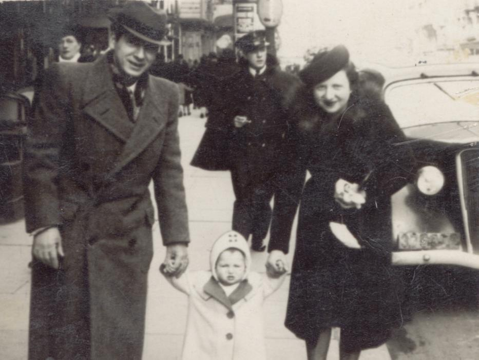 Jacques and Fajga Aizenberg with their daughter, Josiane, walks down the street hand in hand, circa 1941.