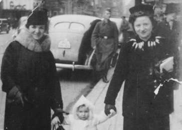 Fajga Aizenberg (right), her mother, and Fanny's daughter, Josiane, walk down the street hand in hand, circa 1941.