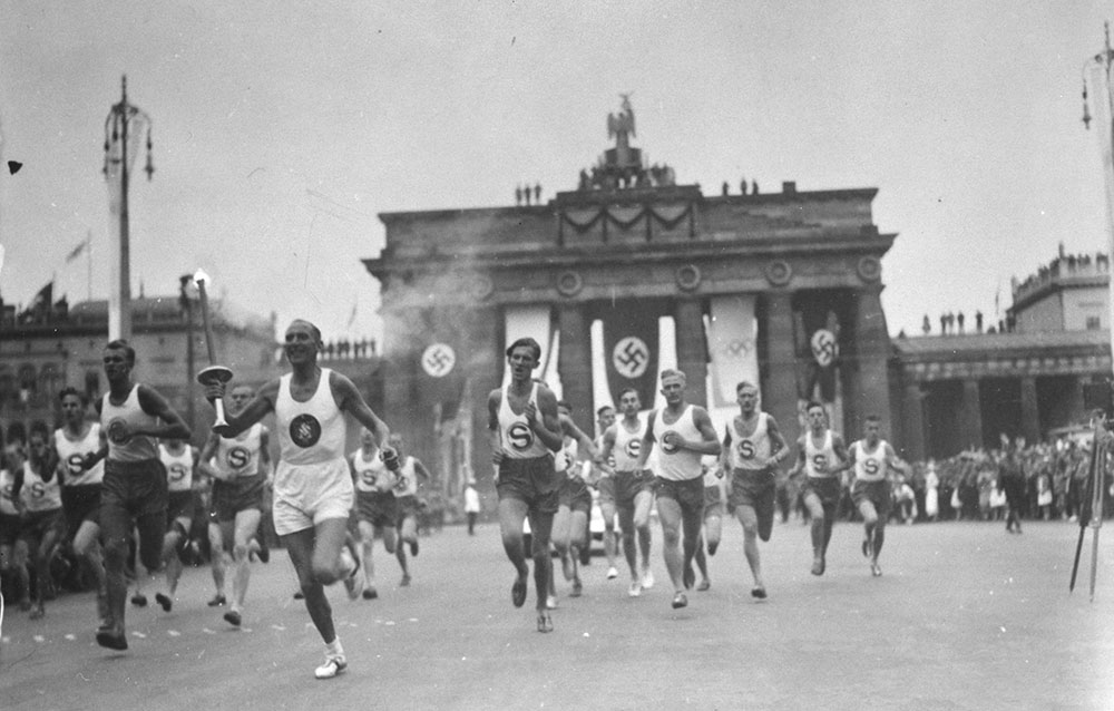 The Olympic torch bearer running through Berlin, passing by the Brandenburg Gate.