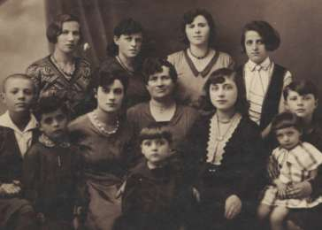 Studio portrait of an extended prewar Jewish family in Poland. Manya Moskowicz is standing on the far right.