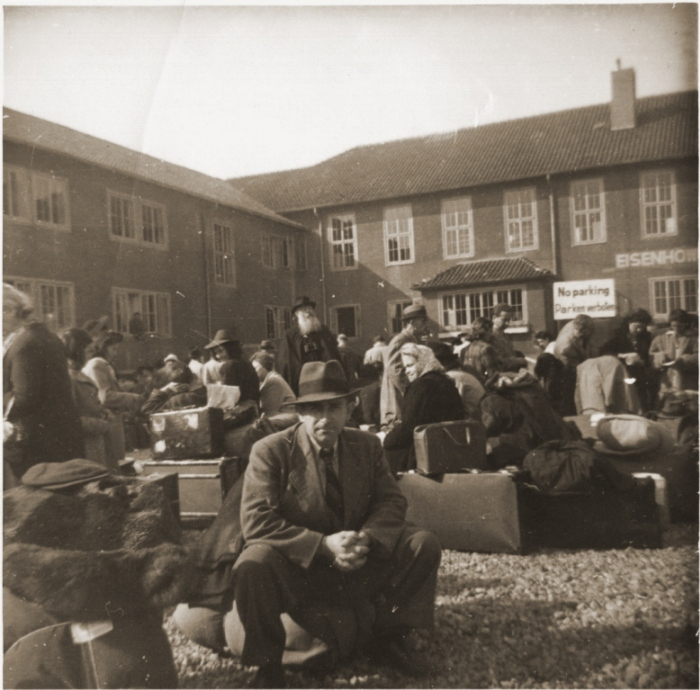 Displaced persons departing Germany for the United States wait with their luggage in the former Von Tirpitz navy yard. In May 1946, the ship <i>Marine Flasher</i> transported 867 European DPs to New York City, the first contingent admitted under President Truman's December 1945 directive expediting the immigration of displaced persons to the US. Bremen, Germany, May 1946.