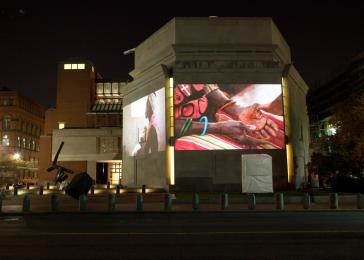Photographs from a bearing witness trip to South Sudan projected onto the exterior walls of the Museum. <i>US Holocaust Memorial Museum</i>