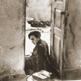 Abba Kovner sits among the ruins of the FPO's former headquarters following the liberation of Vilna.