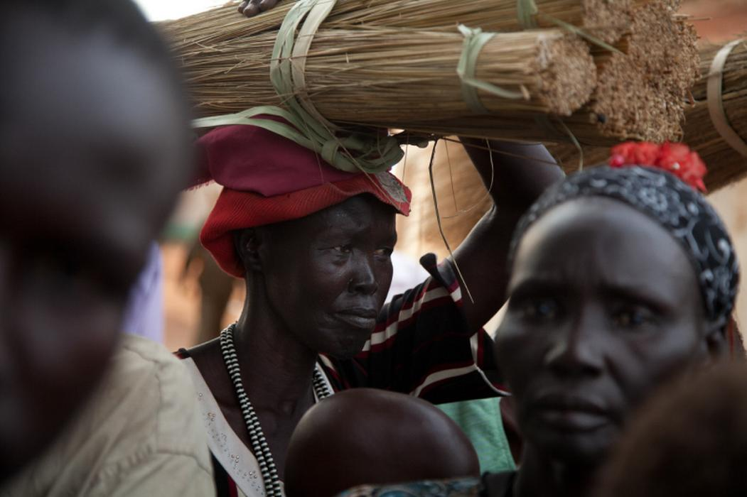 A woman carries her purchase from the local market in downtown Rumbek, South Sudan. <i>US Holocaust Memorial Museum, gift of Lucian Perkins</i>