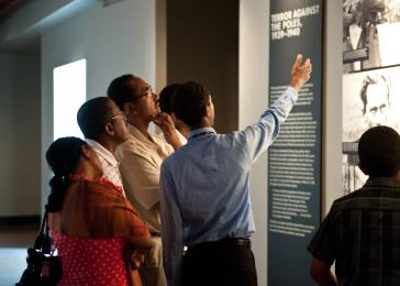 Participants in the Bringing the Lessons Home program tour their family and friends through the Permanent Exhibition. <i>US Holocaust Memorial Museum</i>