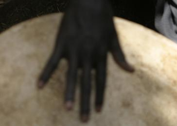 Hand on a drum. Gidel, the Nuba Mountains. December 2004. <i>James Nicholls for US Holocaust Memorial Museum.</i>