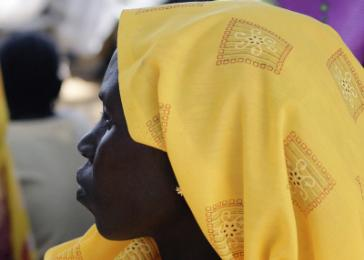 Nuba woman in yellow, Eucharistic celebration. An easing of the war-time Nuba isolation has meant the resumption of trade with Arab merchants from the North&#8212;hence the availability of fabric and other consumer goods from the North. Kauda, the Nuba Mountains. December 2004. <i>James Nicholls for US Holocaust Memorial Museum.</i>