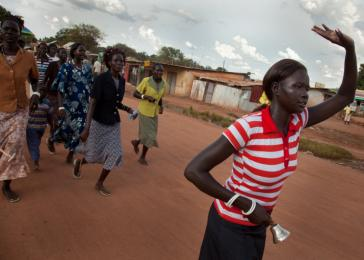 Women dance in the streets of Rumbek, South Sudan, as they head to a wedding. <i>US Holocaust Memorial Museum, gift of Lucian Perkins</i>