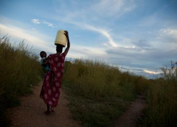 24-year-old Sunday Achan carries her son and water to her home. Sunday and her parents fled Sudan during the North-South civil war. October 11, 2010.
