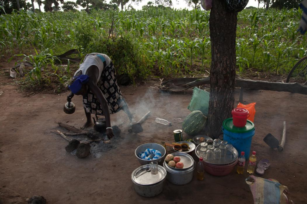 At the Women for Women International center in Rumbek, South Sudan, women learn to grow and market a variety of crops on community land. Here, one woman helps to prepare food for the staff and students. <i>US Holocaust Memorial Museum, gift of Lucian Perkins</i>