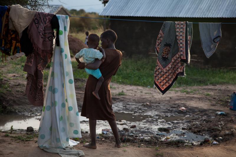 Sunday&#8217;s niece Mary holds Sunday&#8217;s one-year-old son Sam nearby Sunday&#8217;s home in a village outside of Juba, South Sudan. <i>US Holocaust Memorial Museum</i>