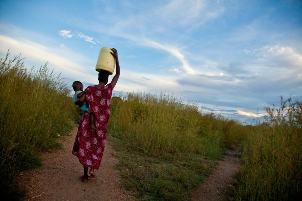 24-year-old Sunday carries her son and water to her home. Sunday and her parents fled Sudan during the North-South civil war. They ended up in a Ugandan refugee camp, where Sunday, her mother, and her sister were captured by the Lord&#8217;s Resistance Army (LRA). Sunday witnessed them being killed by the LRA and was badly hurt herself. She escaped with her sister&#8217;s two children, whom she now raises with her own in a small village outside of Juba, South Sudan. <i>US Holocaust Memorial Museum, gift of Lucian Perkins</i>