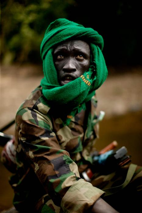 A young SPLA-N rebel watches northern air strikes from the relative safety of a dry creek bed in Blue Nile State. <i>Pete Muller for US Holocaust Memorial Museum</i>