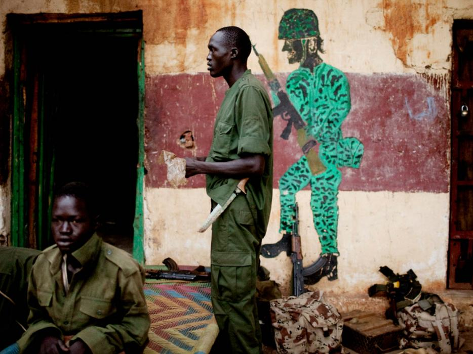 SPLA-N fighters outside their base near the town of Kurmuk, in Blue Nile State, Sudan. <i>Pete Muller for US Holocaust Memorial Museum</i>