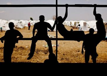 Nuba boys take refuge from the sun under one of the only structures in the Pariang refugee camp along the border between Sudan and South Sudan. <i>Pete Muller for US Holocaust Memorial Museum</i>