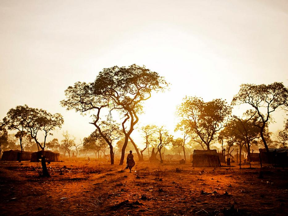 A female refugee from South Kordofan walks through the Yida refugee camp at dawn. Owing to the oppressive heat, most refugees in Yida aim to accomplish more strenuous tasks during the early morning and evening hours. <i>Pete Muller for US Holocaust Memorial Museum</i>