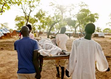 Men carry an extremely sick girl to the only medical center in the Yida refugee camp in Unity State, South Sudan. <i>Pete Muller for US Holocaust Memorial Museum</i>