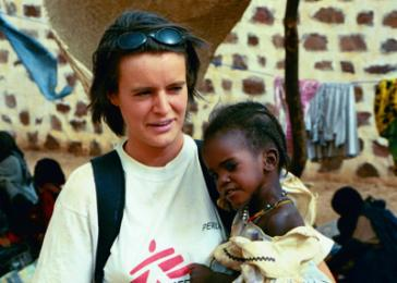 """Jamel, une cadeau de Touloum."" Virginie Cauderlie, a nurse with Doctors without Borders/Medecins sans Frontieres, holds Jamel, a ""gift from Touloum"" for the therapeutic feeding center run by MSF in Iriba, Chad. May 2004. <i>US Holocaust Memorial Museum</i>"