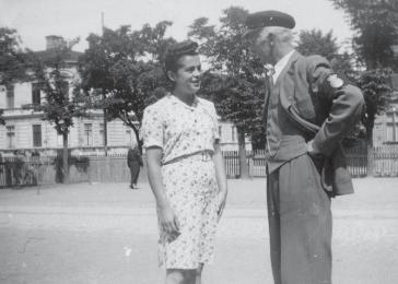 Manya Friedman in her first civilian dress after the war, speaking to a security officer at a school in Lund, Sweden. Courtesy of Manya Friedman.