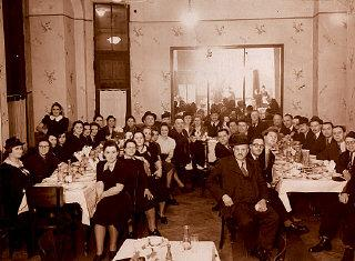 Photograph taken during the engagement party of Agnes' uncle. Agnes' mother is seated along the left wall (fifth from front) and her father along the right wall (third from front). Budapest, Hungary, 1939.
