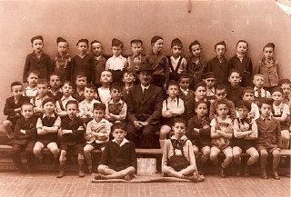 Vilmos (Agnes's brother) is pictured in the third row, second from the left, of this portrait of his first year elementary school class. Budapest, Hungary, 1937–1938.