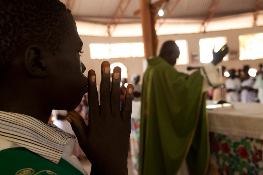 An alter boy prays during a service, at the Holy Family Parish Church in Rumbek, South Sudan. <i>US Holocaust Memorial Museum, gift of Lucian Perkins</i>