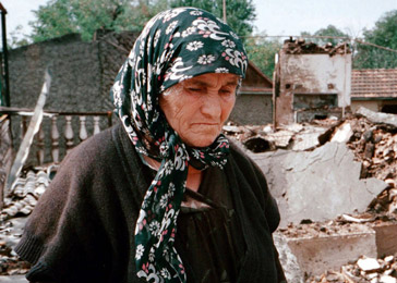 Aset Musayeva stands in the ruins of her home in the Chechen village of Alleroy. August 28, 2001.
