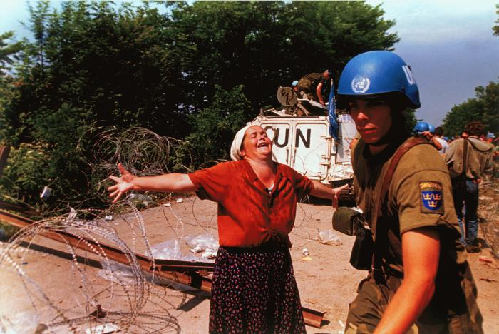 A Bosniak woman at a makeshift camp for people displaced from Srebrenica in July 1995. <i>US Holocaust Memorial Museum, gift of Ron Haviv/VII.</i>