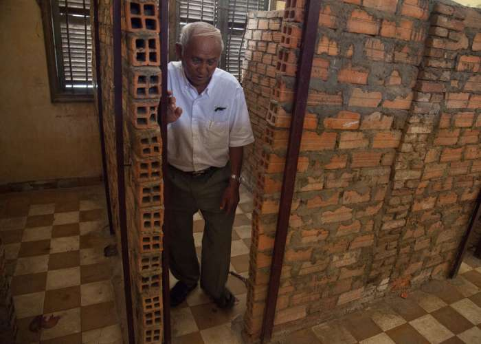 Chum Mey shows where his cell was in the prison, which is now the Tuol Sleng Genocide Museum. He goes to the Museum several times a week to tell his story to visitors and sell his book about his life during the Khmer Rouge regime. October 2012.
